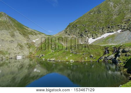 Beautiful view of high mountain lake. Landscape from Capra Lake in Romania and Fagaras mountains in the summer.
