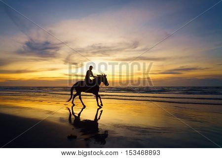 Silhouette of horse rider against the ocean and a sunset in Sabah Malaysian Borneo.