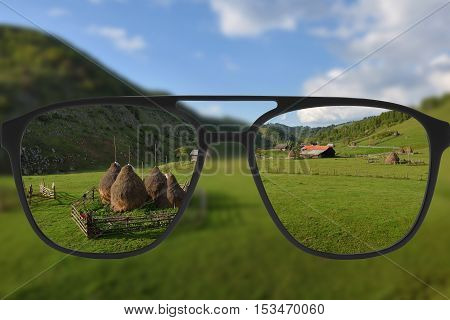 Clear image in glasses against blurry landscape