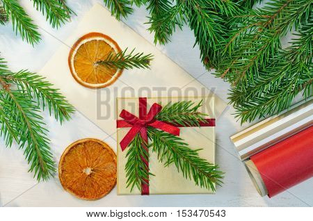 Christmas gift, envelope and package items - christmas tree branches, box, paper, - with copy space. Packaging of christmas gift. Overhead view. Christmas mood photo