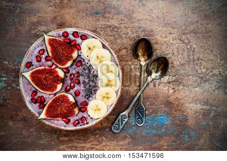 Healthy fall and winter breakfast set. Acai superfoods smoothies bowl with chia seeds pomegranate sliced banana fresh figs and hazelnut butter. Overhead top view. Copy space