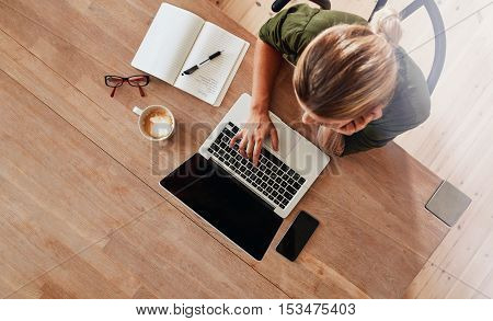 Top view of woman using laptop while sitting at cafe table with laptop mobile phone diary coffee cup and glasses. Female surfing internet at coffee shop.