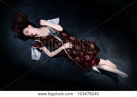 Fantasy woman lying on the ground with sword over dark background