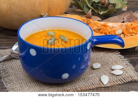 Cup Of Homemade Pumpkin Soup Close Up On Background Of Pumpkin