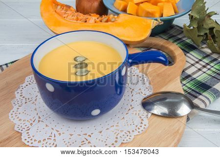 Pumpkin Soup In A Blue Tureen On Cutting Board