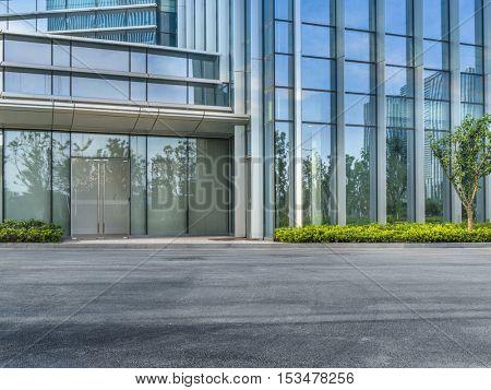 empty asphalt road by modern office building.