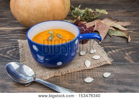 Blue Cup Of Pumpkin Soup And Pumpkin On A Background Of Autumn Leaves
