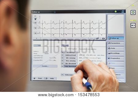 A doctor is checking a readings from a pacemaker on a monitor.