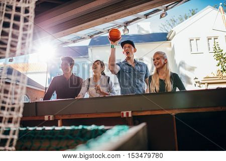 Young man throwing basketball in hoop with friends at fair. Young people playing basketball game at amusement park.