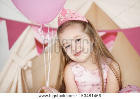 portrait of little girl on the day of birth in a dress with colorful balloons. Kid girl wearing pink crown celebrating her birthday