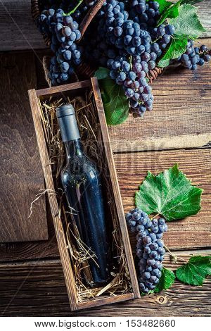 Red wine in bottle in old wooden box