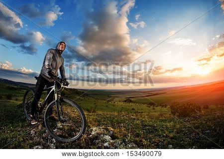 Young Man Cycling In A Summer Meadow At Sunset
