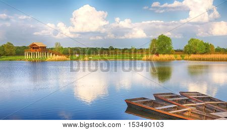 Summer season landscape. Stilt house and three wooden boats. The place is one of the backwaters of the Tisza river in Tiszalok, Hungary. Cloudy blue sky and forest green. Warm dry calm weather.