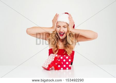 Angry young woman in santa claus costume sitting and shouting over white background