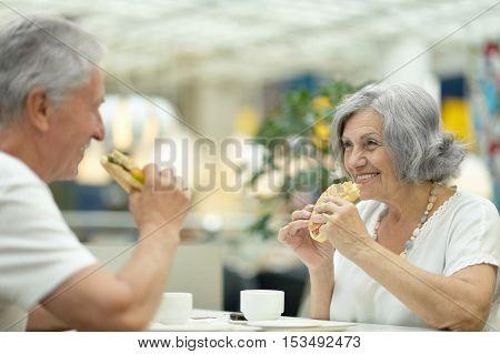 Portrait of beautiful elderly couple eating fast food