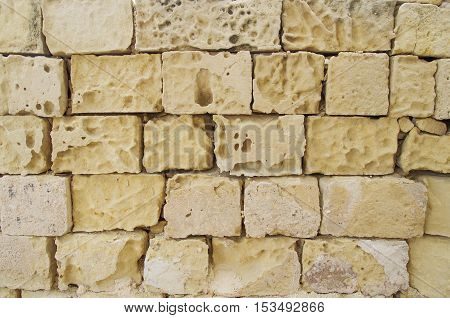 Yellow coquina bricks wall with wide seams
