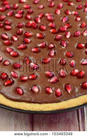 Homemade baked chocolate tart with pomegranate arils