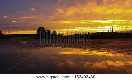 the reflection of the sunset in a puddle on the road