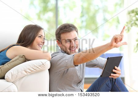 Happy couple sitting and planning new decoration with a tablet on line at home with a window in the background