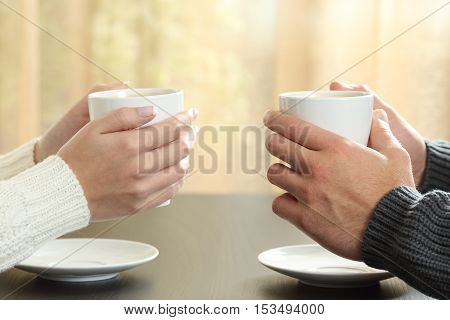 Profile of hands of a couple holding coffee cups over a table in winter in an apartment with a window in the background