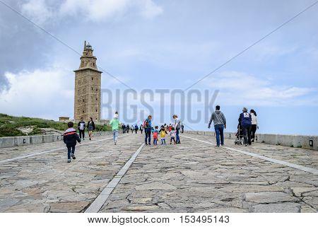 La Coruna Spain - May 28 2016: People walking on promenade towards Hercules tower Torre de Hercules roman lighthouse UNESCO world heritage Coruna Galicia Spain.