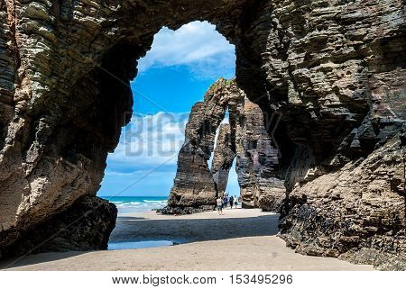 A Coruna Spain - May 29 2016: Turists under Natural rock arches Cathedrals beach (playa de las catedrales) Spain Atlantic ocean. Famous beach in Northern Spain. Natural rock arch on Cathedrals beach in low tide (Cantabric coast Lugo (Galicia) Spain).