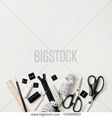 Everything for sewing in black and white. Fabric and thread zipper and buttons scissors and centimeter pencil and ruler.
