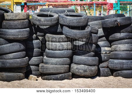 Worn, old and damaged rubber tires dumping outdoors
