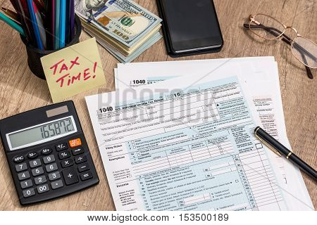 tax form with calculator money and pen