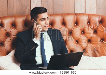 Happy businessman talking on the phone, free space. Business and finance concept. Investment. Coworking.