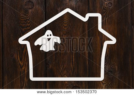 Halloween holiday. Paper haunted house with ghost. Copyspace, abstract conceptual image. Dark wooden background