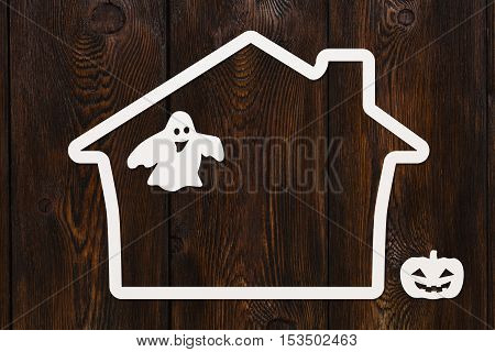 Halloween holiday. Paper haunted house with ghost and pumpkin. Copyspace, abstract conceptual image. Dark wooden background