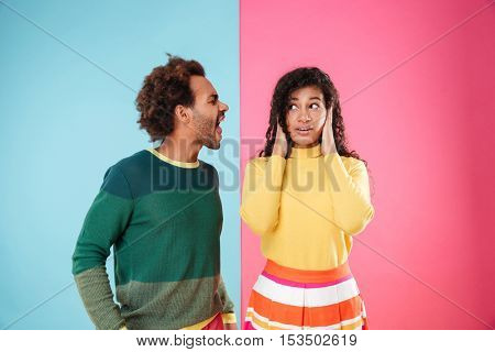 Angry african american young couple shouting on his girlfriend with covered ears