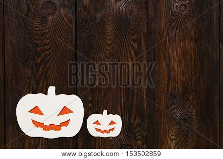 Halloween holiday. Two paper smiling Grand Pumpkins. Dark wooden background, copyspace. Abstract conceptual image