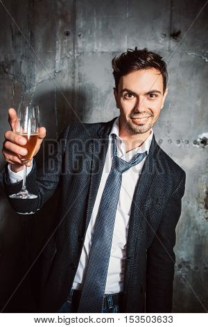 Handsome man in suit toasting at xmas corporate party on gray background. Giving good christmas toast at holiday event