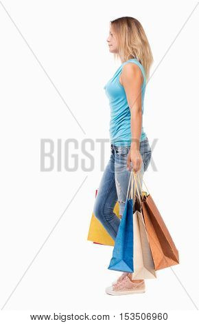 back view of going  woman  with shopping bags . beautiful girl in motion.  backside view of person. . Isolated over white background.  The blonde in a blue sweater misses with colored bags