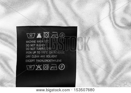 Washing instructions clothes label on white satin as a background