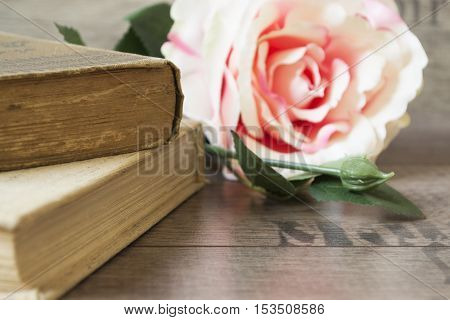 Old Books And Flower Rose On A Wooden Background. Romantic Floral Frame Background. Picture Of A Flo
