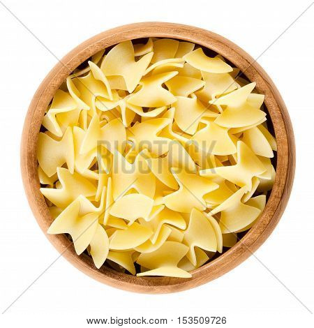 Uncooked egg noodles in wooden bowl over white. Specialty in traditional Austrian cooking, also called Fleckerl. Butterfly shaped noodles made from durum semolina and eggs. Isolated macro food photo.