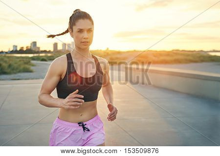 Beautiful and toned female jogger with swinging ponytail and pink shorts running in city park during sunrise. Includes copy space.