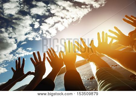 Friendship team concept with lots of hands reaching to the sun