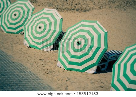 Green and white striped parasols lined up on the beach