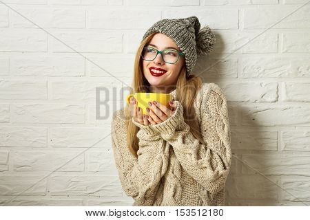 Happy Smiling Hipster Girl in Knitted Sweater and Beanie Hat with a Mug in Hands. Beautiful Woman at White Brick Wall Background. Winter or Autumn Warming Up Concept. Toned Photo with Copy Space.