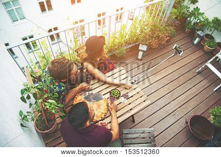 Overhead view of three friends on patio taking photo using device with long attachment