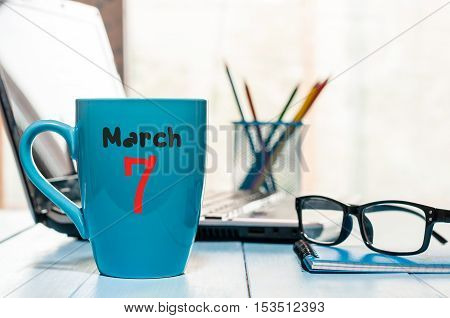 March 7th. Day 7 of month, calendar on business office background, workplace with laptop and glasses. Spring time, empty space for text.
