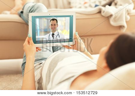 Pregnant woman video chatting with doctor on tablet. Professional medical online consultation concept.