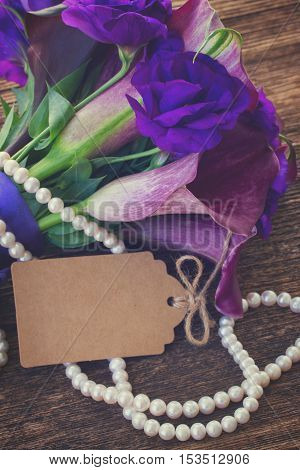 Bouquet of calla lilly and eustoma flowers on wooden table with empty paper note, retro toned