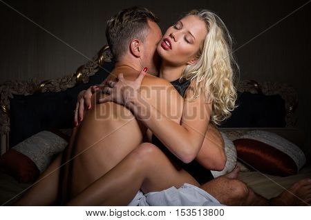 Man kissing woman's neck in bedroom before making love