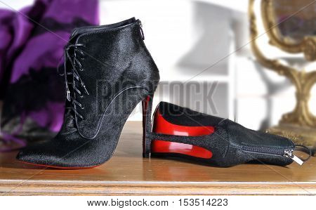 Ukraine Kiev - August 25 2016: Women's boots handmade. imitation brand shoes Christian Louboutin showing red soles - illustrative editorial