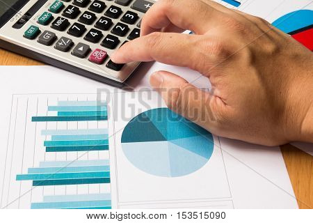 Business man press on calculator with financial chart and graph